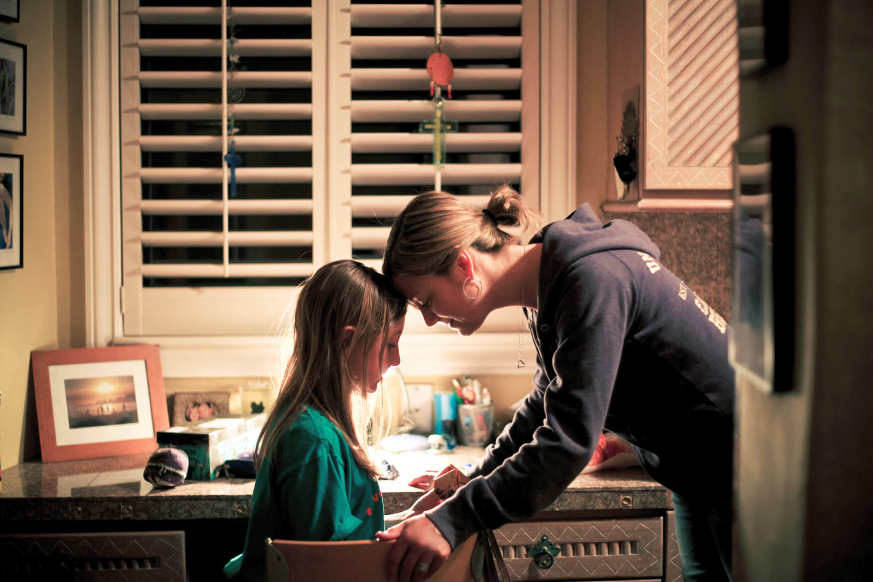 mother standing next to daughter sitting at desk with their foreheads pressed against each other